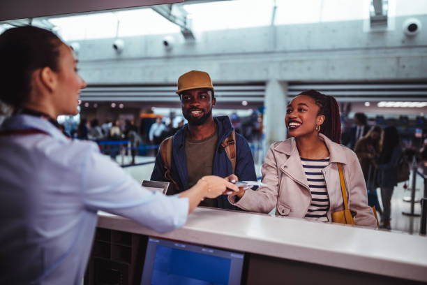 young passengers doing check-in for flight at airport - airport check in counter stock pictures, royalty-free photos & images