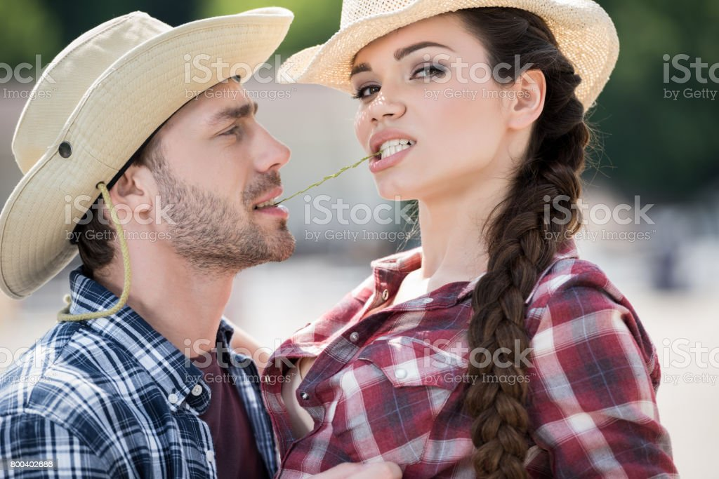 young passionate cowboy style couple embracing with straw stock photo