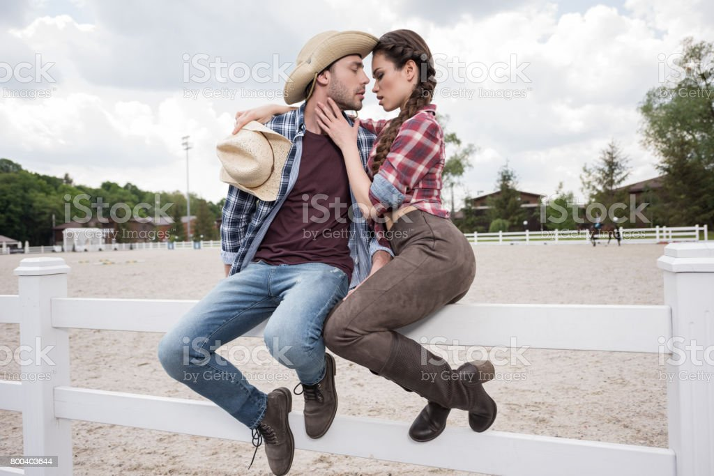 young passionate cowboy style couple kissing while sitting on fence at ranch stock photo
