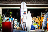 Quirky Portrait of entrepreneur, artist, and business owner shows off one of his latest custom built surfboards.