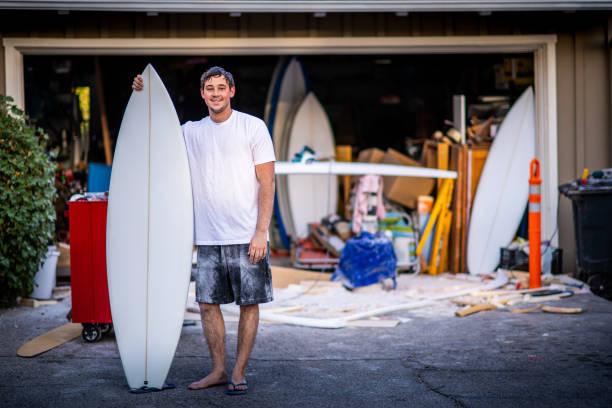 unga passionerad entreprenör visar upp sin avslutade custom surfbräda - surf garage bildbanksfoton och bilder
