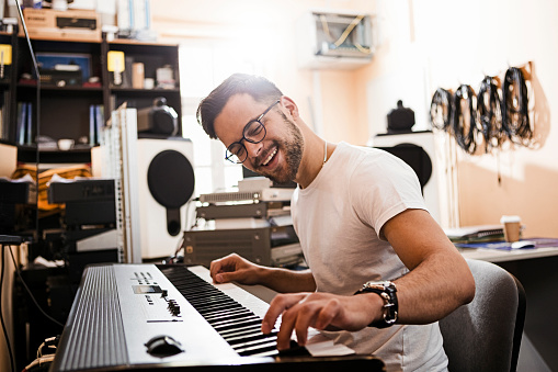 Young man playing electric piano ,recording in studio