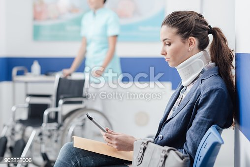 Young female patient with cervical collar support at the hospital, she is sitting in the waiting room and connecting with a digital tablet, medical staff working on the background