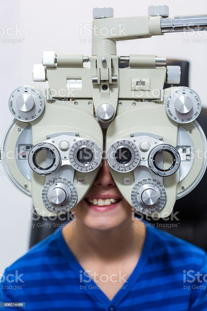 Young patient looking through phoropter during eye examination stock photo