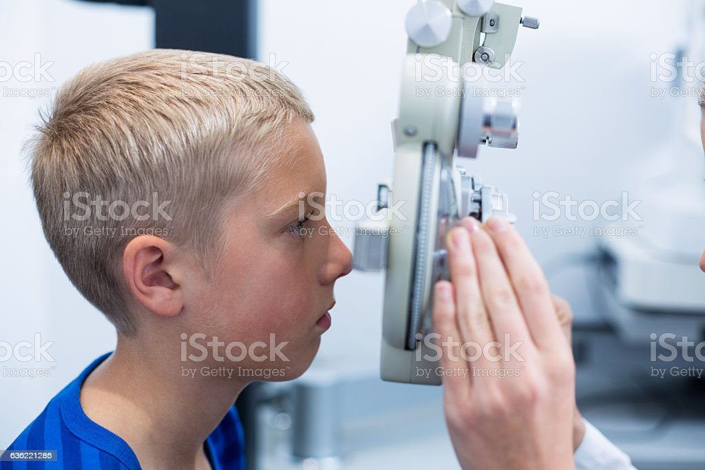 Young patient under going eye test through phoropter stock photo