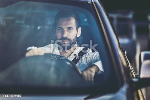 Young businessman going to work by car and thinking of something.