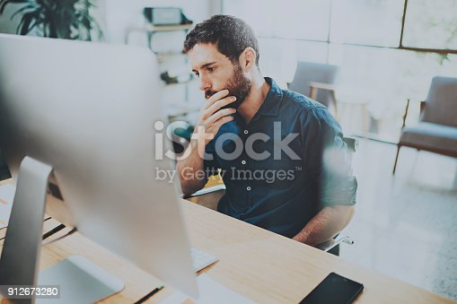 istock Young pensive businessman working at sunny office while sitting at the wooden table.Man analyze document on desktop computer.Blurred background. 912673280