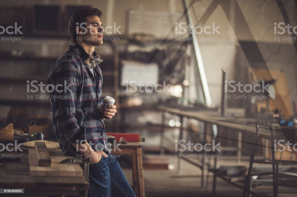 Young pensive carpenter having a coffee break in a workshop. stock photo