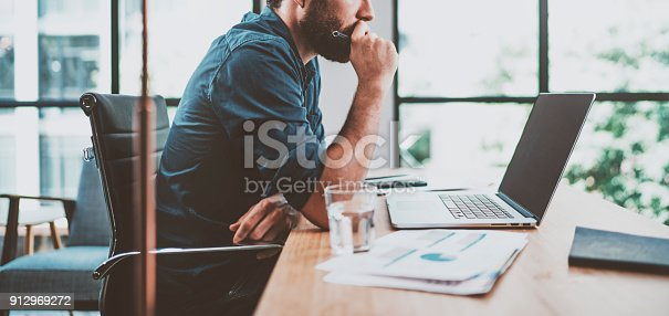 istock Young pensive coworker working at sunny work place loft while sitting at the wooden table.Man analyze document on laptop display.Blurred background.Horizontal wide. 912969272