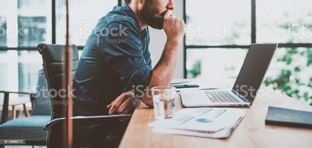 Young pensive coworker working at sunny work place loft while sitting at the wooden table.Man analyze document on laptop display.Blurred background.Horizontal wide. stock photo