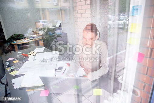 Young pensive coworker working at sunny work place. Man analyze project on laptop display.