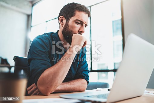 istock Young pensive man working at sunny office on laptop while sitting at wooden table.Businessman reports on notebook computer.Blurred background,horizontal. 912952490