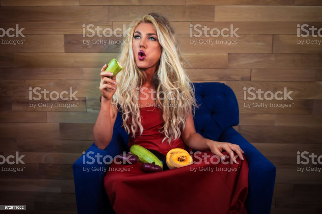 Young pensive vegetarian woman sits on armchair on background of...
