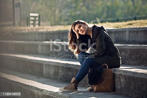 istock Young pensive woman day dreaming on staircase in the park. 1135416023