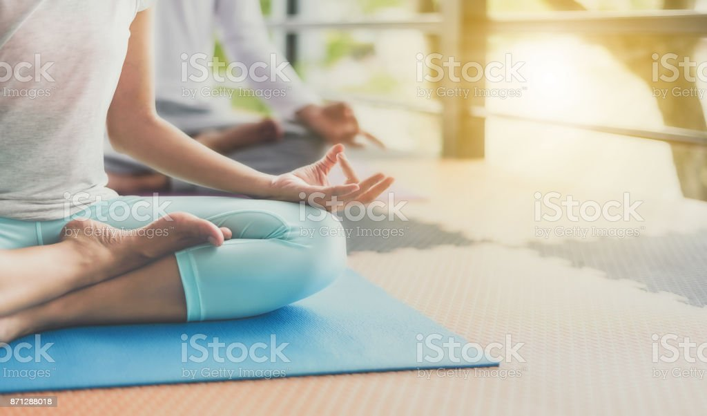 Young people are meditating on colorful tires for good health. stock photo