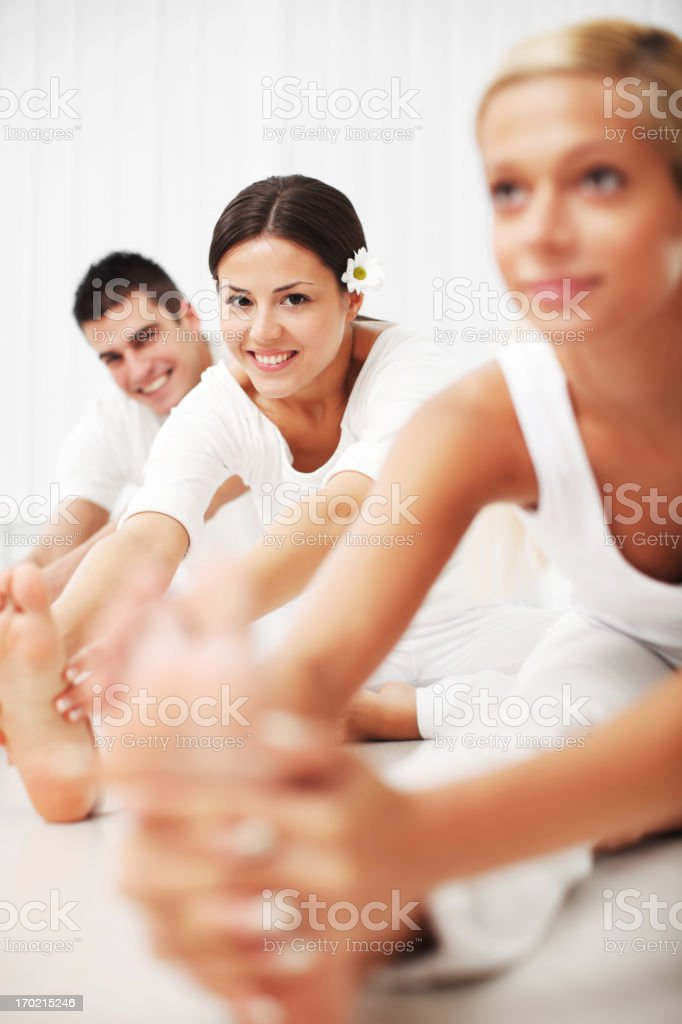 Young people are stretching, doing a yoga exercise. royalty-free stock photo