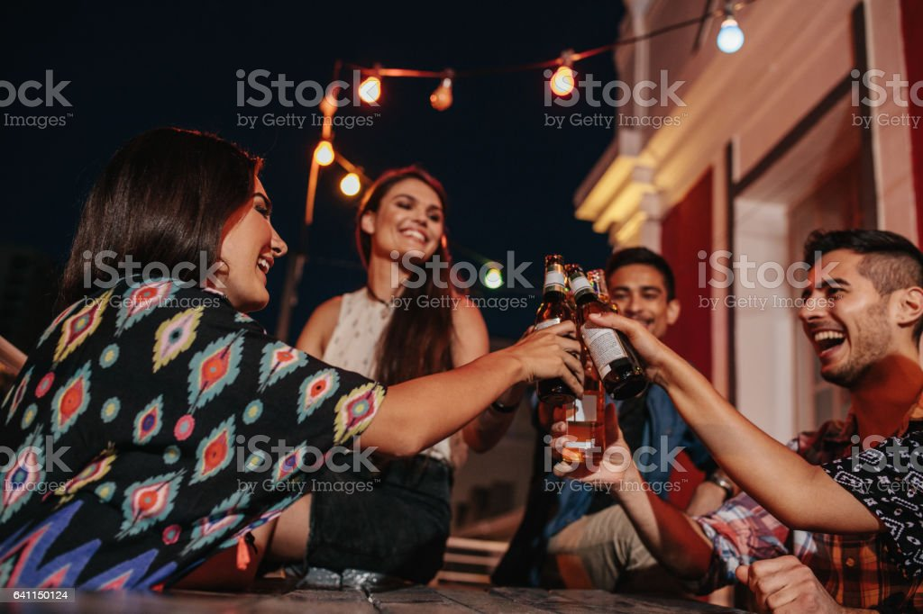 Young people at party toasting beers stock photo
