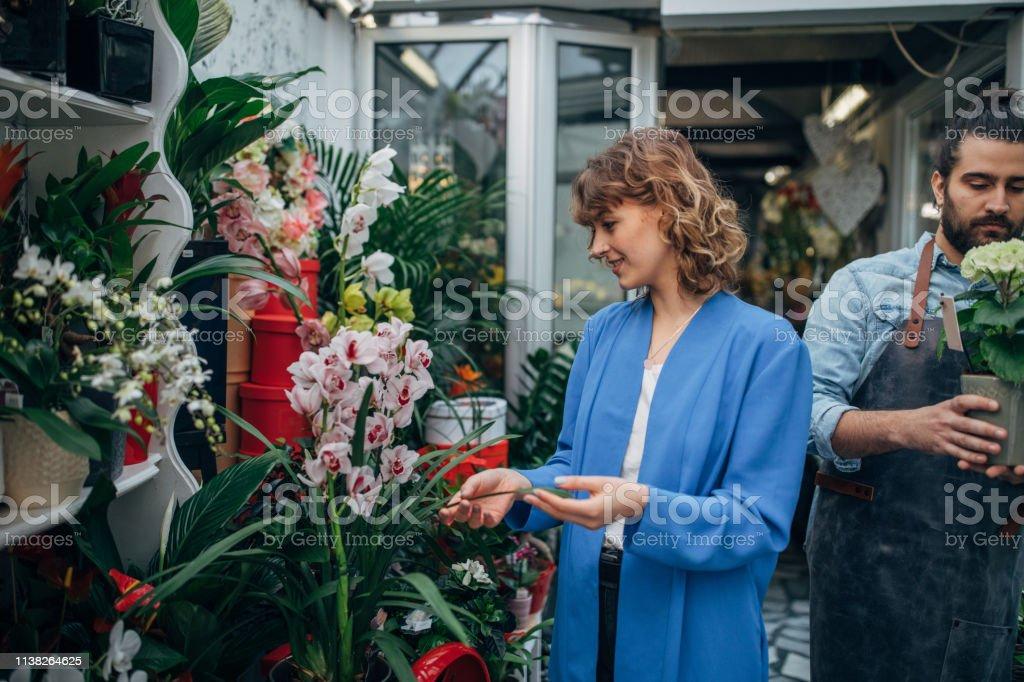 Customer at the flower shop looking at plants and florist in the back.