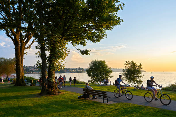 young people biking and walking at stanley park - public park stock photos and pictures