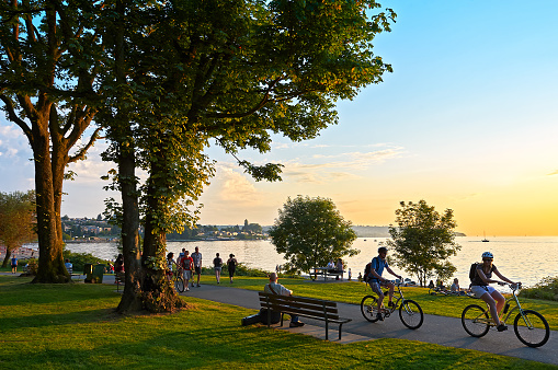Young couple cycling, others walking or jogging late afternoon and enjoying the sunset at Stanley Park Vancouver, British Columbia, Canada