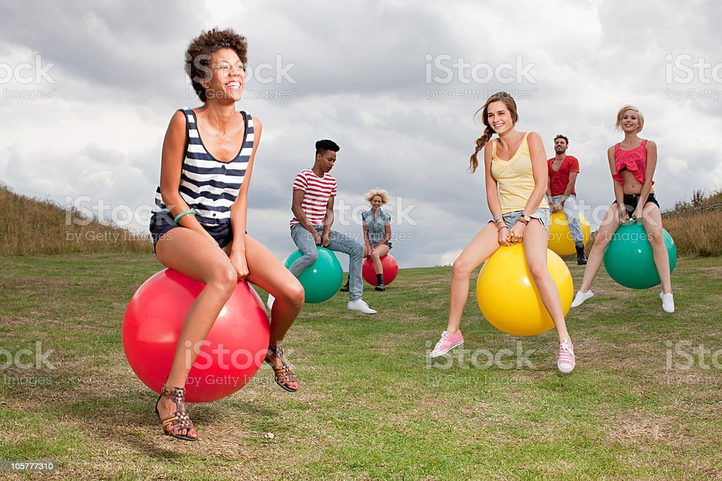 Young people bouncing on hoppity horses stock photo