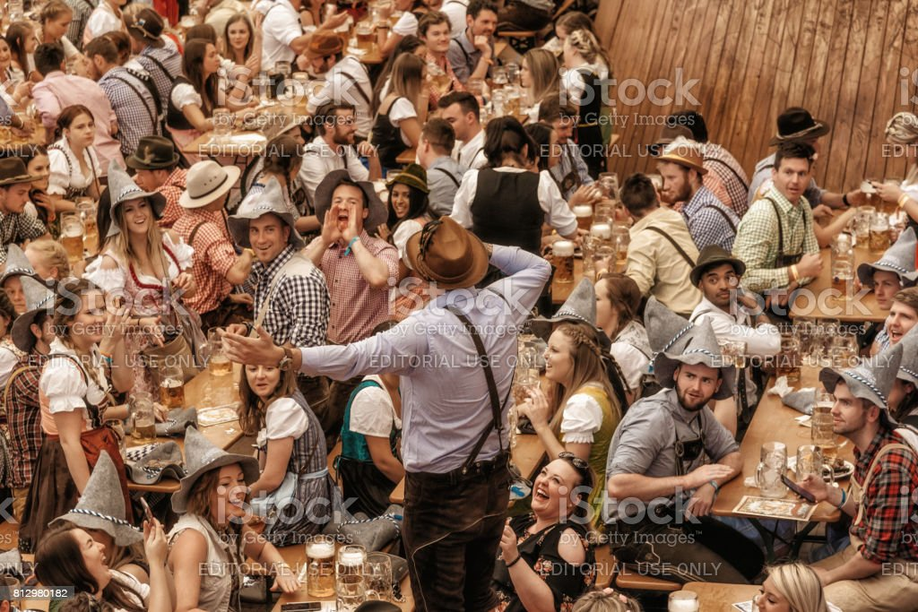 young people celebrating in beer pavilion on Oktoberfestfest in Munich stock photo