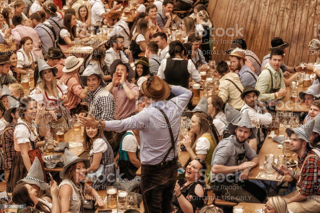 jóvenes, celebrando en el pabellón de la cerveza en Oktoberfestfest en Múnich - foto de stock