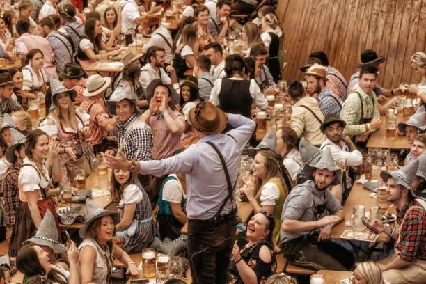 jóvenes, celebrando en el pabellón de la cerveza en oktoberfestfest en múnich - oktoberfest fotografías e imágenes de stock
