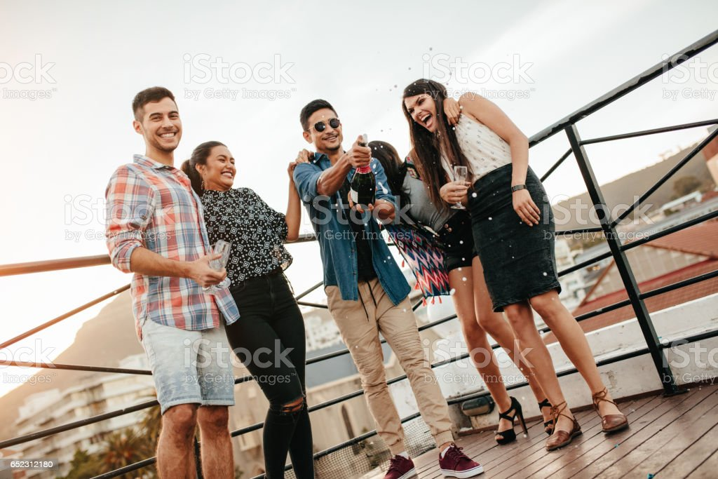 Young people celebrating with champagne at party on rooftop stock photo
