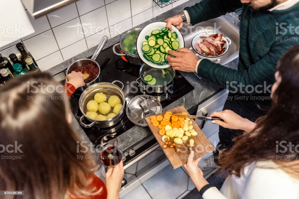 young people cooking together stock photo