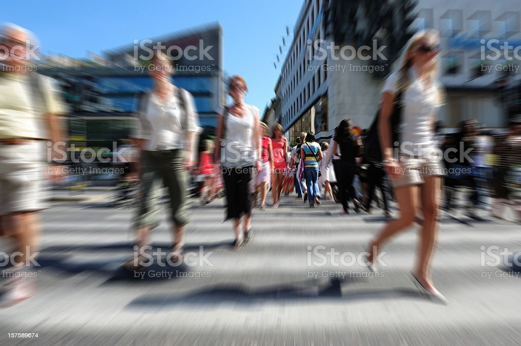 Young people crossing sunlit street, motion blur royalty-free stock photo