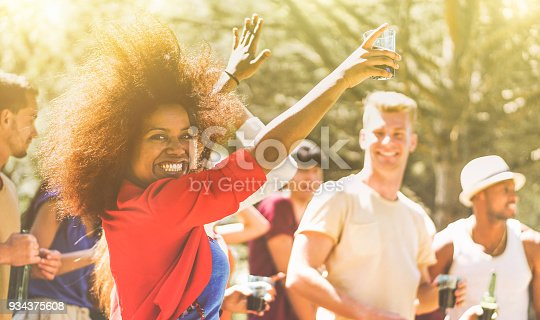 istock Young people dancing in forest party on summer time - Happy friends drinking cocktails and laughing together outdoor in music festival - Focus on black girl face - Youth lifestyle and event concept 934375608