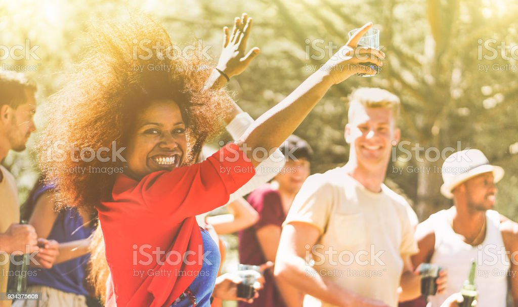 Festa de jovens dançando na floresta no horário de verão - felizes amigos beber cocktails e rindo juntos ao ar livre no festival de música de estilo de vida - foco no rosto da garota negra - juventude e conceito de evento - foto de acervo