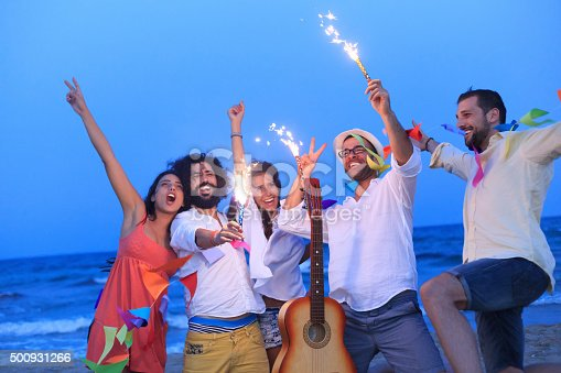 471113366istockphoto Young people dancing on the beach with fireworks 500931266