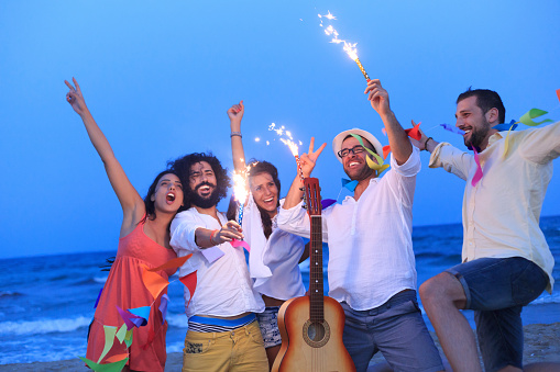 471113366 istock photo Young people dancing on the beach with fireworks 500931266