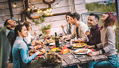 istock Young people dining and having fun drinking red wine together on balcony rooftop dinner party - Happy friends eating bbq food at restaurant patio - Millannial life style concept on warm evening filter 1181460583