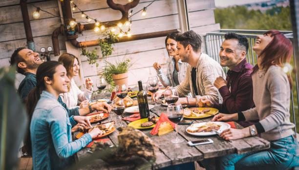 Young people dining and having fun drinking red wine together on balcony rooftop dinner party - Happy friends eating bbq food at restaurant patio - Millannial life style concept on warm evening filter stock photo