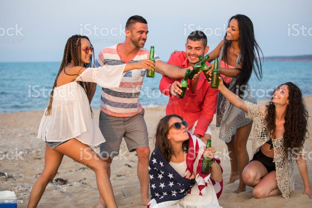 Young people drinking beer and celebrating on beach royalty-free stock photo