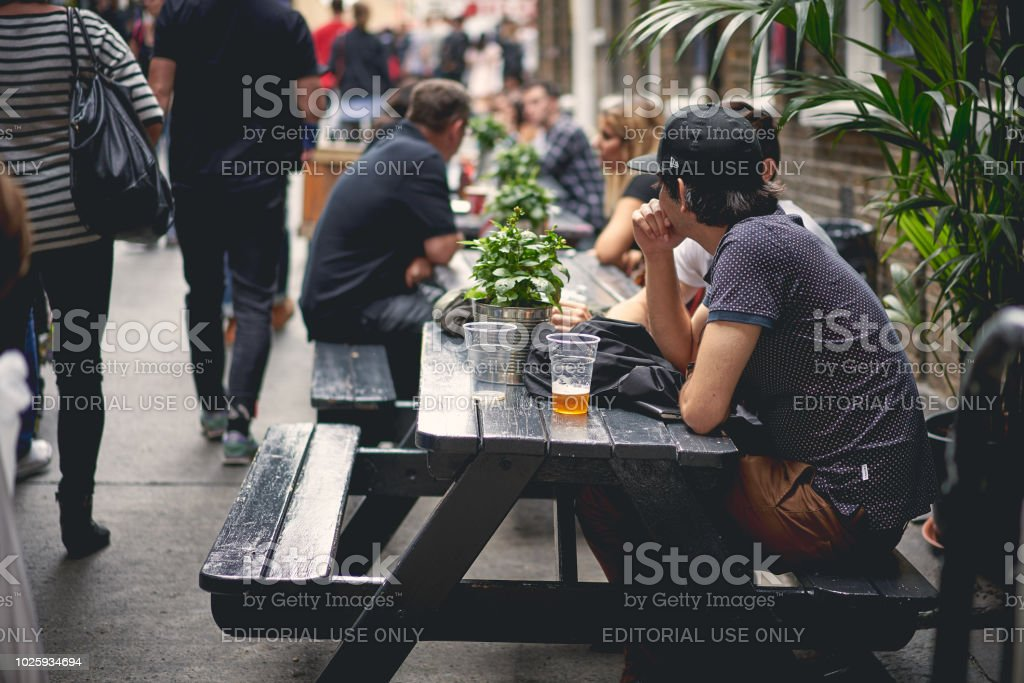 Young people drinking beer in a pub in Brick Lane, Shoreditch (London). stock photo