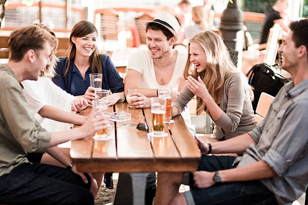 Young people drinking beer outdoors stock photo