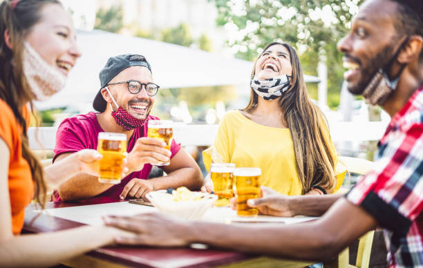 Young people drinking beer with open face masks - New normal lifestyle concept with friend having fun together talking on happy hour at brewery bar - Bright vivid filter with focus on left guy stock photo