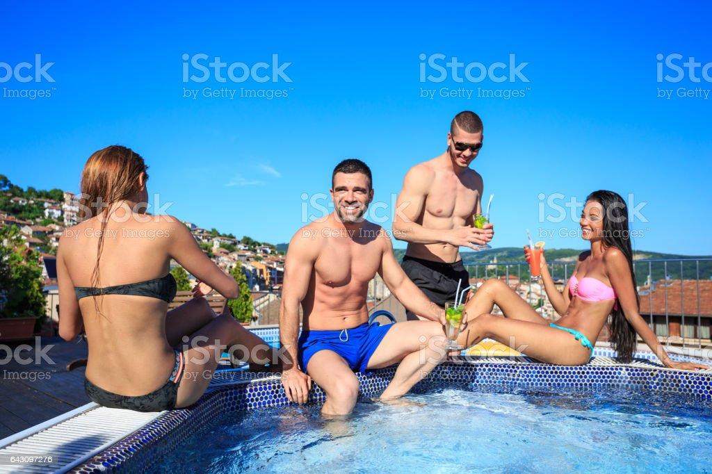 Jeunes gens, boire des cocktails sur la piscine sur le toit - Photo