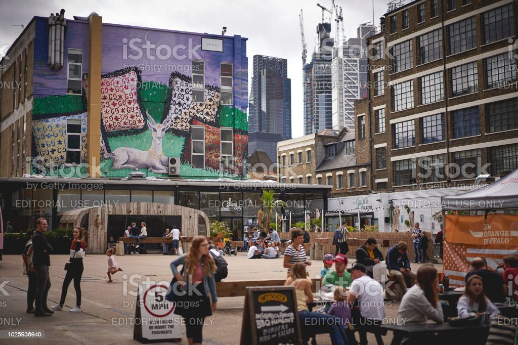 Young people drinking outdoor in Brick Lane, near Shoreditch (London). stock photo