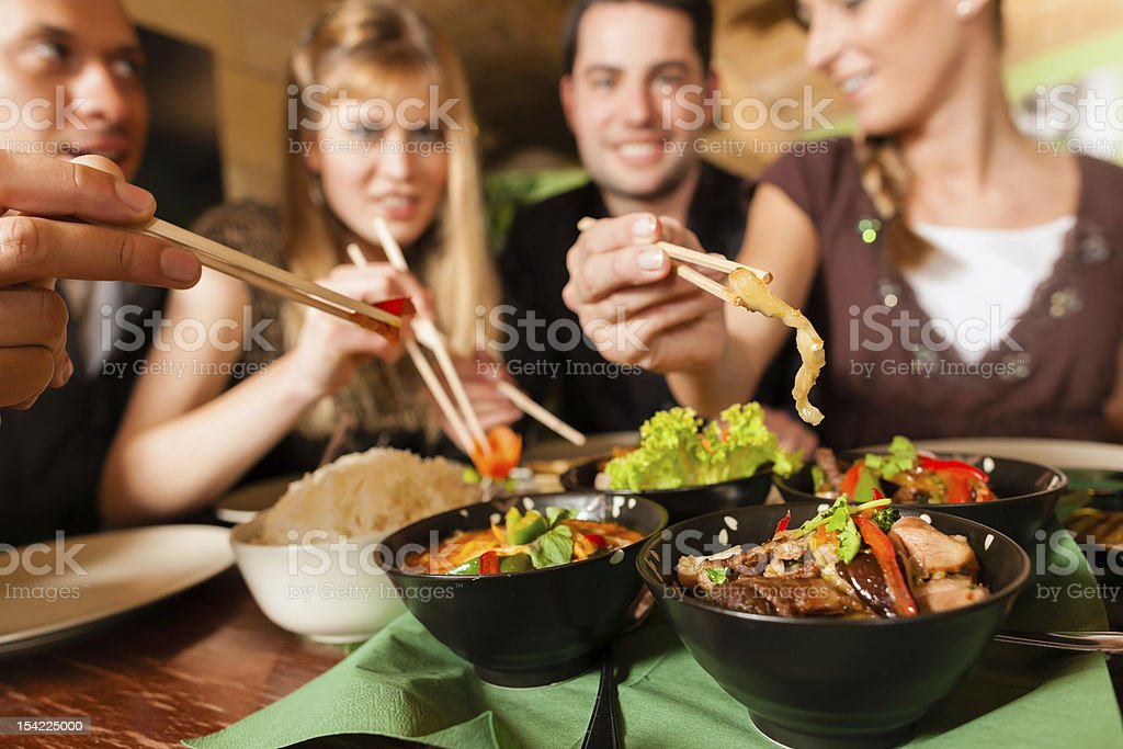 Young people eating assorted dishes at Thai restaurant stock photo