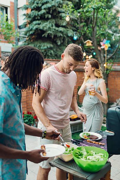 junge menschen essen im barbecue-party. - paletten terrasse stock-fotos und bilder