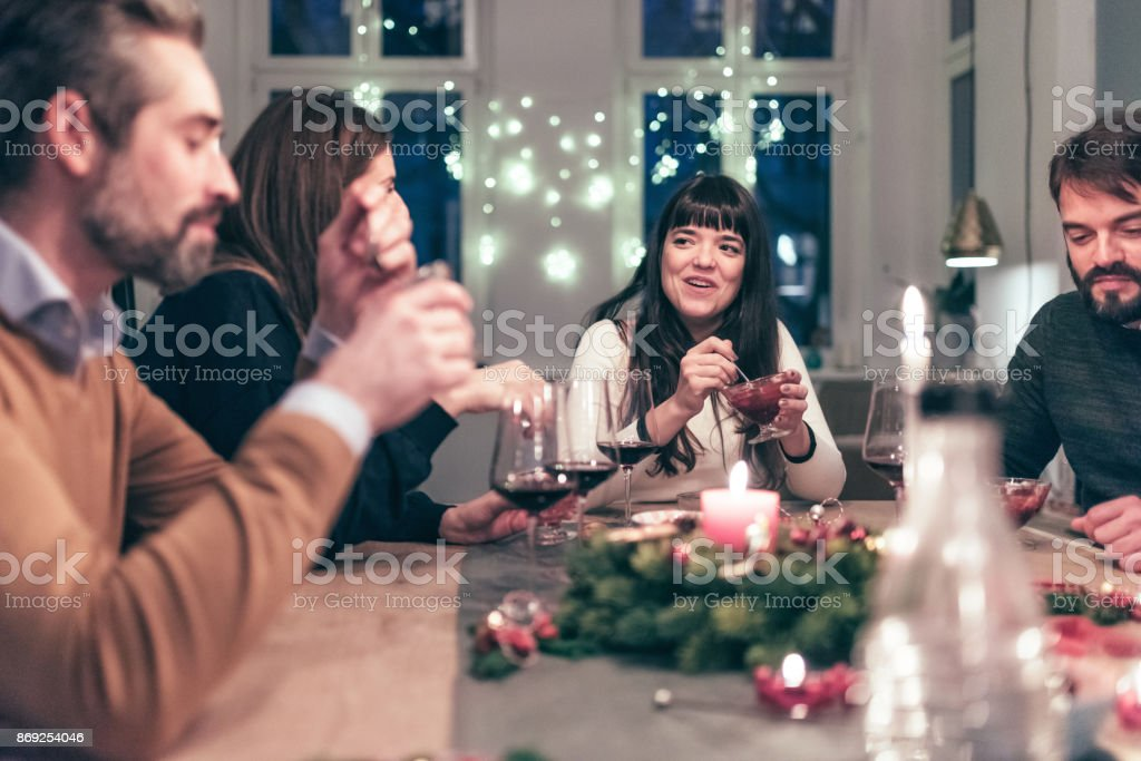 young people eating dessert at christmas table at night