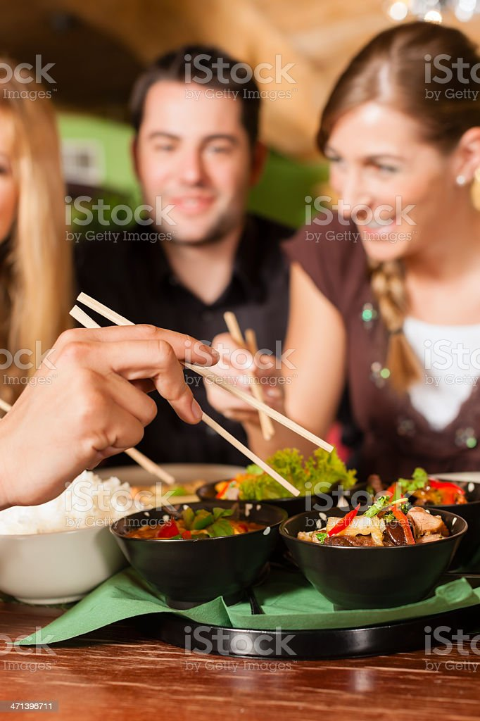 Young people eating in Thai restaurant royalty-free stock photo
