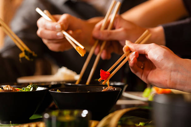 Young people eating in Thai restaurant Four sets of chopsticks grabbing Asian food out of various black bowls sitting on a table in a Thai food restaurant.  Three pairs of chopsticks have food between them, and one is in a black bowl.  There is a person's chest out of focus in the background.  There are four sets of chopsticks visible, but there are only three hands visible.  There is a set of chopsticks coming into view from the left.  The hand in front is in focus, while the two hands in the background are slightly blurred. asian food stock pictures, royalty-free photos & images