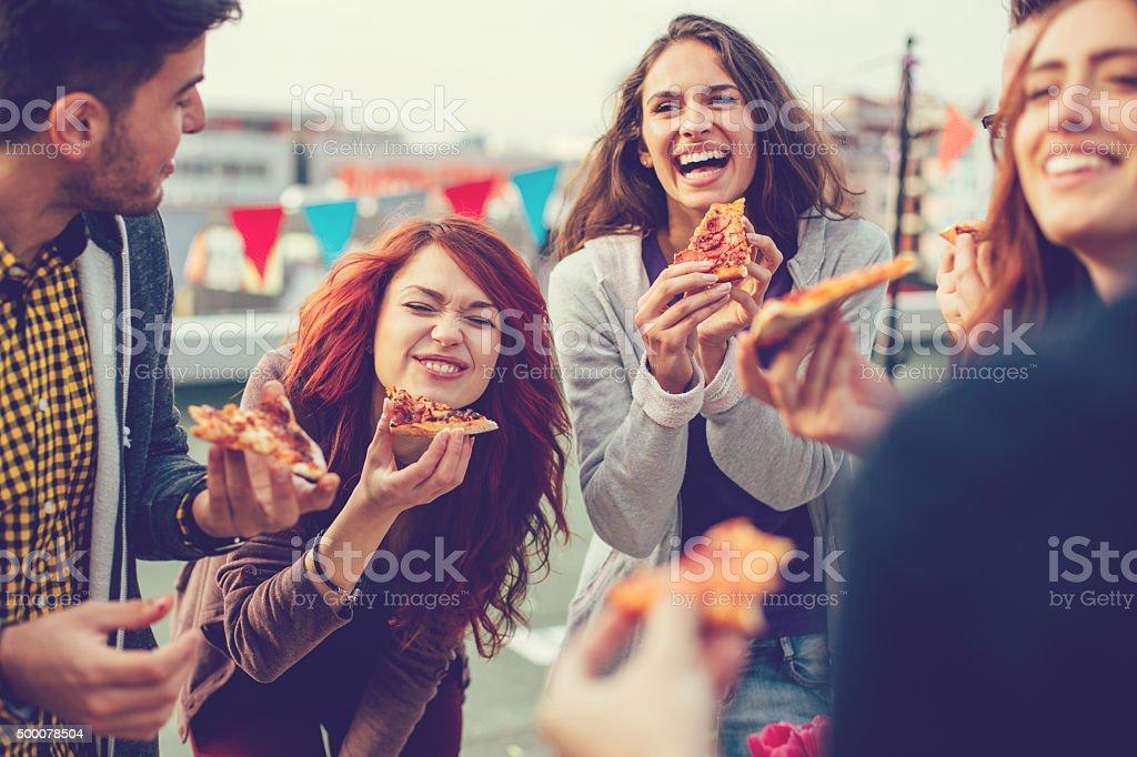Молодой человек едят пиццу в стороны стоковое фото