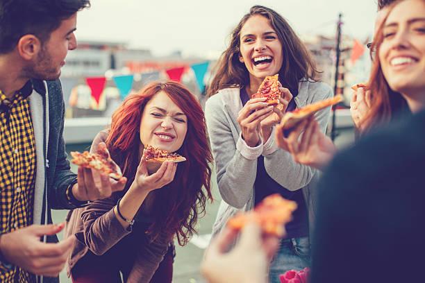 jóvenes de comer pizza en fiesta - couple lunch outdoors fotografías e imágenes de stock